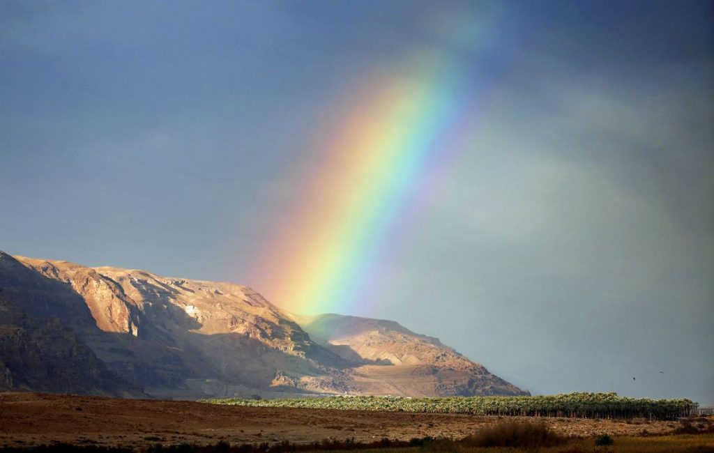 A rainbow rises from the mountains near the Dead Sea.